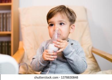 Little boy using steam inhaler nebulizer mask inhalation at home. Medical procedures vapor medication treatment asthma pneumonia bronchitis coughing