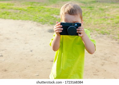 Little boy using vintage camera. Cute caucasian child taking photo with old retro film camera