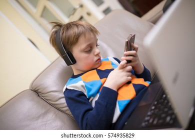 Little boy using a white  laptop computer at home along with mobile phone, wearing headphones, playing some games.