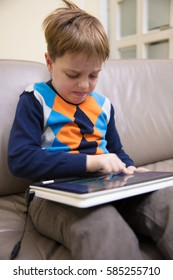 Little boy using a white laptop computer at home, playing some games.