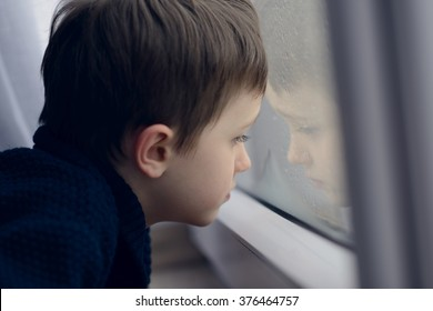 Little boy waiting by window for stop raining. Loneliness and waiting concept. Rainy day