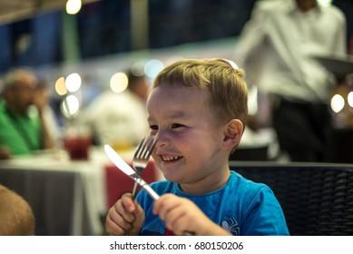 Little boy waiting for his dinner at restaurant