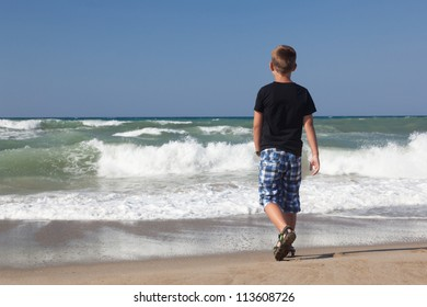 A little boy walking alone on the beach. Blue sky and brown sand. Waves.