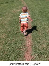 Little boy walking away on a path in the grass