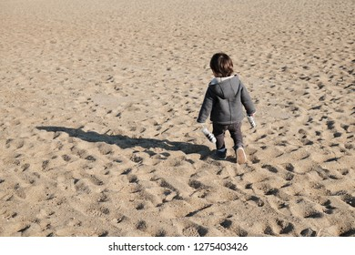 Little boy walking on beach during winter sunny day