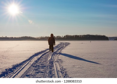 Little boy walking on the lake ice in Finland. There's a lot of snow. The sun shines brightly from the front.