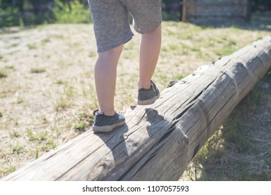 Little boy walking on a log in the park. child on the balance beam