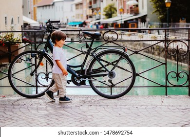 Little boy walking over bridge of Thiou River in Annecy, France near parked bicycle. Child in the city. Little tourist, summer lifestyle. Discovering Europe, traveling with kid.