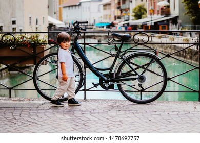 Little boy walking over bridge of Thiou River in Annecy, France near parked bicycle looking at camera. Child in the city. Little tourist, summer lifestyle. Discovering Europe, traveling with kid.