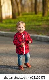 Little boy is walking in a spring park