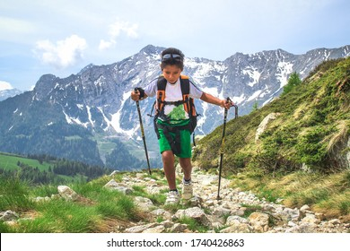 Little boy walks  during an excursion on mountain trail  with the backpack