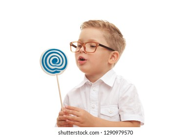 Little boy wants to eat his beautiful lollipop on a white background. Concept of harmful food and caries of milk teeth. Advertising space