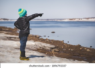 A little boy in warm clothes stands on the shore. The child rejoices at the beginning of spring. The kid raised his hand and points to something in the distance. Spring, joyful mood. Walks in the park