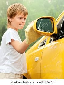 Little boy washing car. Summer. Sunset