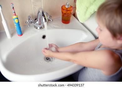 Little boy washing hand in washbasin