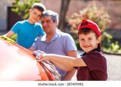 Little boy washing red car with family