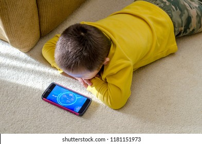 little boy is watching cartoons on moms cell phone on the floor