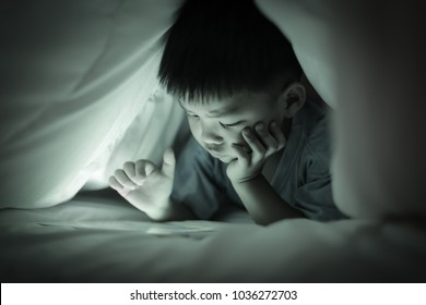 Little boy watching online tablet while lying on bed under white duvet, in the bedroom at night, bright screen light reflex on little child face and his finger hand pointing at  screen. Sepia tone.