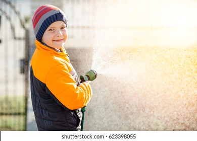Little boy watering flowers with sunset background