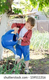 Little boy watering the vegetables standing in the shade of a tree in the veggie garden on a hot summer day pouring from a large blue plastic watering can
