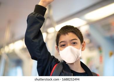 Kleiner Junge trägt Maske schützt vor Viren, die Elektrofahrkarten kaufen und im öffentlichen Bahnhof spazieren gehen