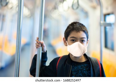 Little boy wear mask protect from virus buying electric ticket and walking in the public sky train station
