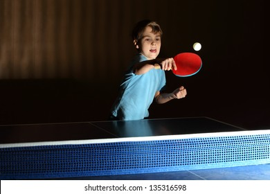 little boy wearing blue shirt playing ping pong; concentrated face; boy stuck out his tongue