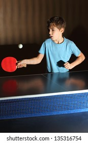 little boy wearing blue shirt playing ping pong; concentrated face; blue net