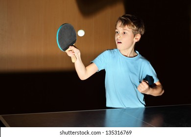 little boy wearing blue shirt playing ping pong; concentrated face