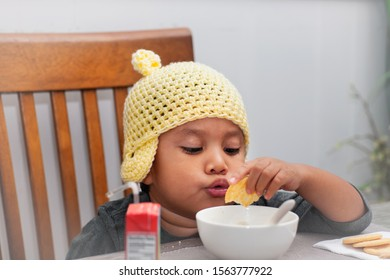 A little boy wearing a crocheted hat is playing with a bowl of soup and crackers because of loss of appetite due to illness.