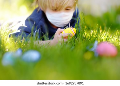 Little boy wearing disposable medical face mask hunting for easter eggs in spring garden on Easter day during coronavirus outbreak. Safety in public place. Focus on multicolor eggs.