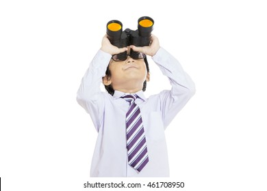 Little boy wearing formal suit and looking through binocular in the studio, isolated on white background