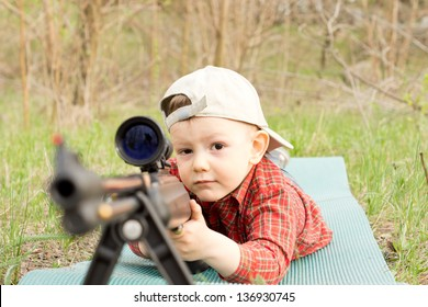 Little boy wearing hat plays with shotgun outdoors
