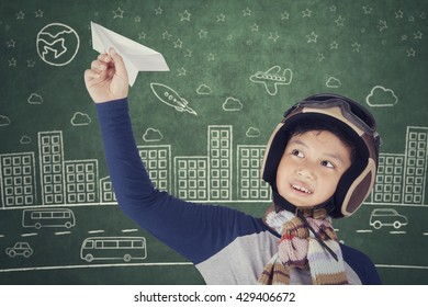Little boy wearing helmet and dreams of becoming an aviator while playing a paper plane
