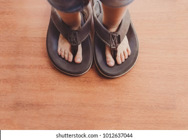 Little boy wearing his dad´s shoes or flip flops.