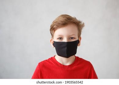 Kleiner Junge mit einer Maske gegen das Corona-Virus covid-19, 2019-nCov. Kind in einem chirurgischen Verband oder Atemschutzgerät während des Ausbruchs des Corona-Virus und der Grippe. Kind in einer medizinischen Maske. Coronavirus-Quarantäne.