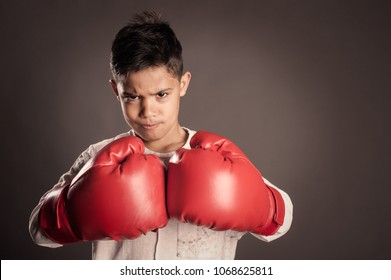 little boy wearing red boxing gloves