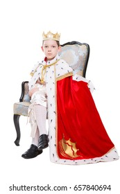 Little boy wearing red costume of a king posing in the throne. Isolated on white