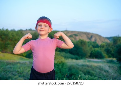 Little boy wearing a red headband standing outdoors showing off his biceps making a fist and flexing his arms
