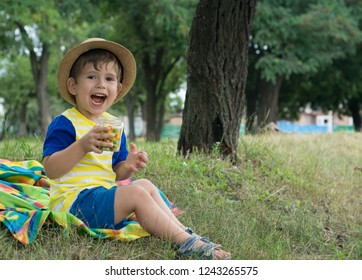 Little boy wearing straw hat eating candy on summer picnic. Box with  colorful candies in 3d7f2ba046de