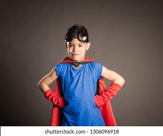 little boy wearing a superhero costume on a gray background