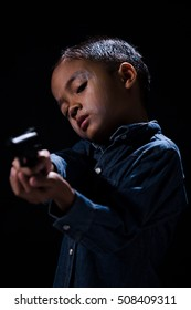 Little boy wearing trendy jeans jacket and shirt, standing on isolated black background.