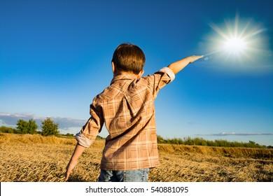 Little boy in wheat field with star.