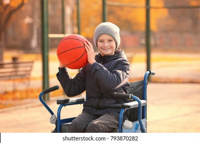 Little boy in wheelchair with ball on playground