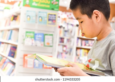 Little boy in wheelchair reading a book in bookstore.