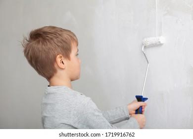 Kleiner Junge beim Malen der Wände im Zimmer.