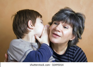 Little boy whispering a secret to his grandmother