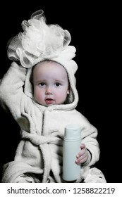 A little boy in a white coat with a hood and washcloth, in the hands of shampoo.