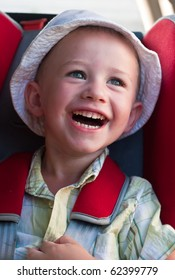 A little boy in white panama hat laughs in a children car seat