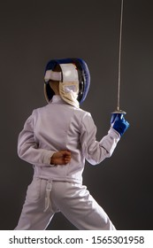 Little boy in a white protective suit fencing mask and with a rapier exercises in fencing on a dark background